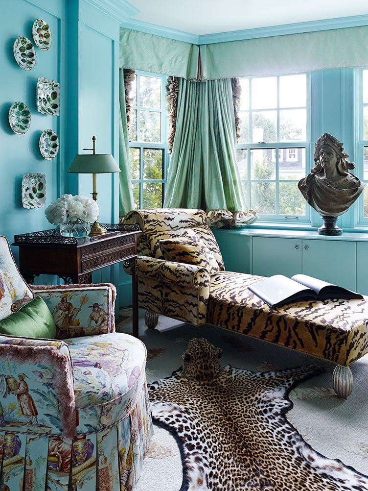 Maximalist Living Room With Clue Walls, Animal Print Sofa Bed and Cheetah Printed Rug.
