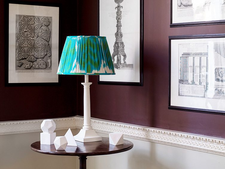 Side Table with Decorative Geometric Sculptures and White Table Lamp with Statement Lampshade.