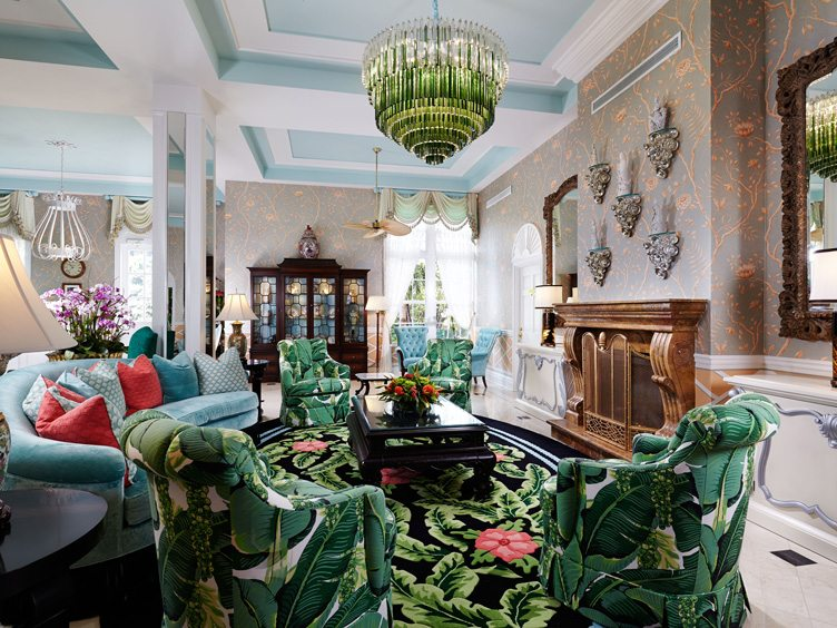 Maximalist Living Room with Green Crystal Chandelier and Leaf Patterned Chairs and Rug.