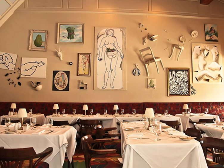 Restaurant Interior With Eclectic Gallery Wall Featuring Nude Female Paintings.
