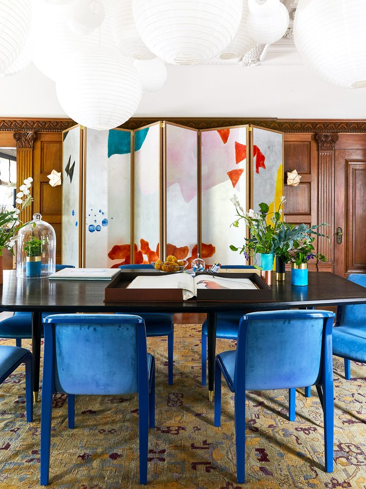 Eclectic Dining Room with Blue Velvet Chairs and Multiple White Hanging Lantern.