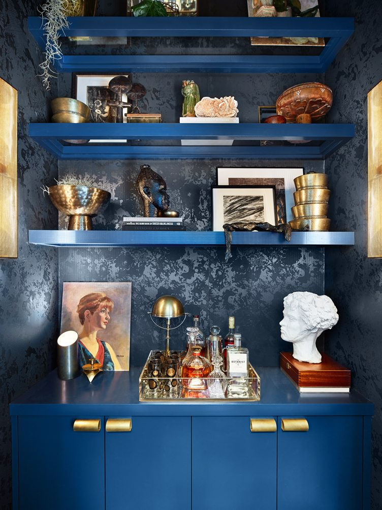 Blue Bookshelf With Brass Bowls, Vintage artwork and photography, and Cocktail Tray.