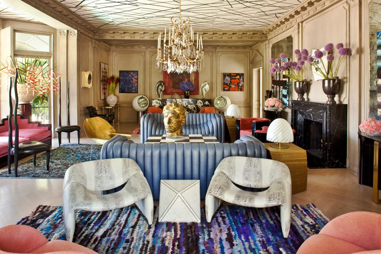 Maximalist living room with hanging chandelier, a gold bust, and a colorful collection of funky furniture.