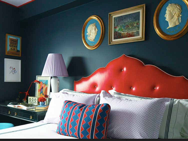 Maximalist Bedroom with Red Leather Headboard an Eclectic Selection of Pillows Against Navy Walls and a Mix of Traditional Hanging Art.