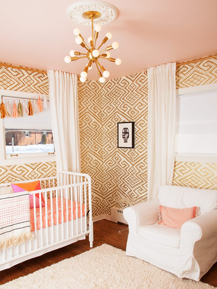 Colorful Baby Nursery With Gold Textile Wallpaper and Gold Sputnik Chandelier.