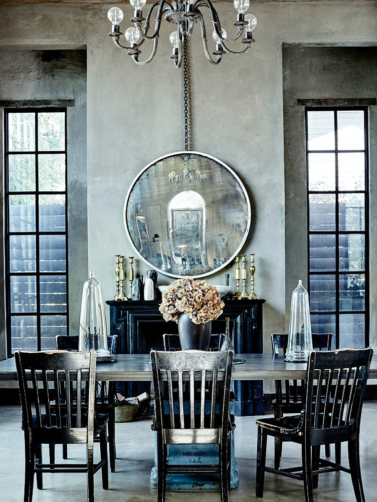 Black ladder, dining chair, and wooden black table under metal chandelier in dining room