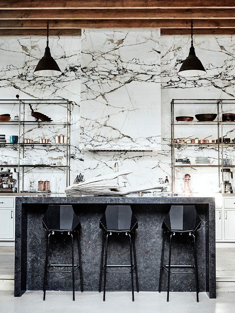 Black barstools, metal shelving, and black granite counter in kitchen