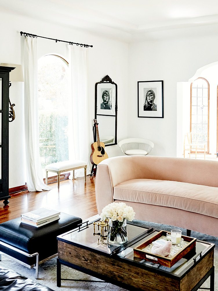 dirty pink sofa with dark blue leather ottoman, and wooden coffee table in living room