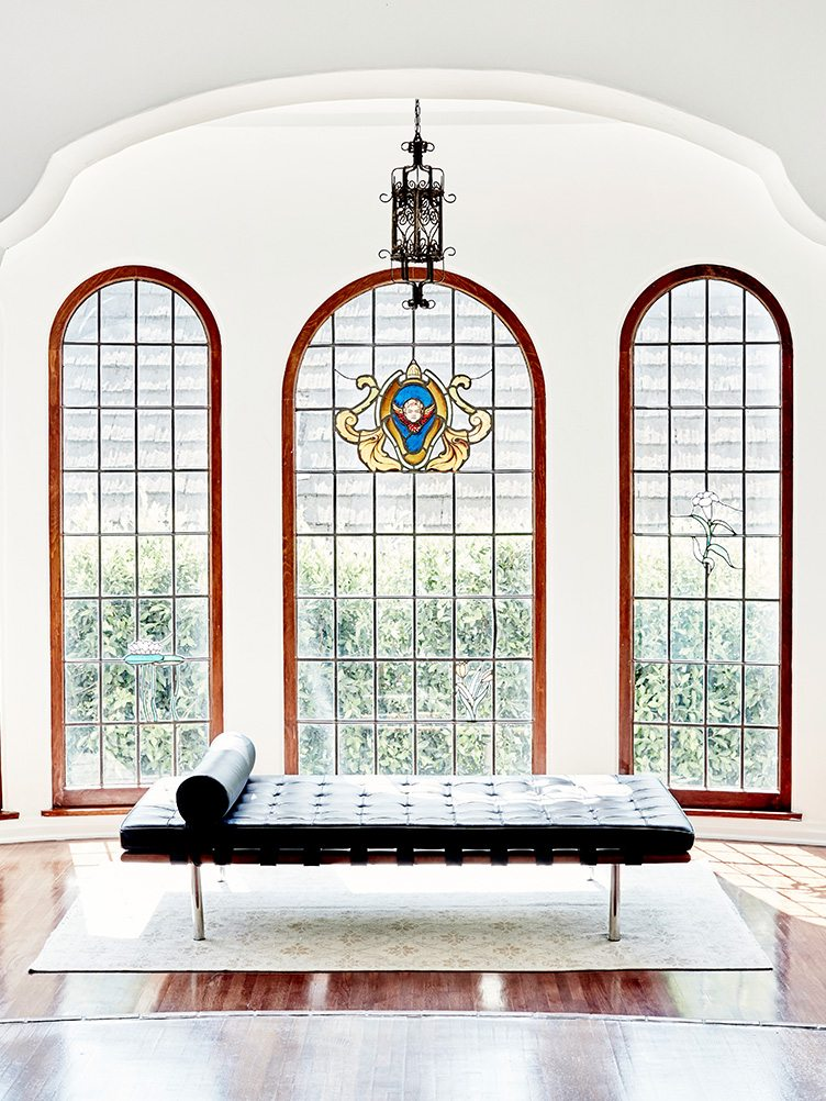 Black leather chair in front of wide windows over oriental rug