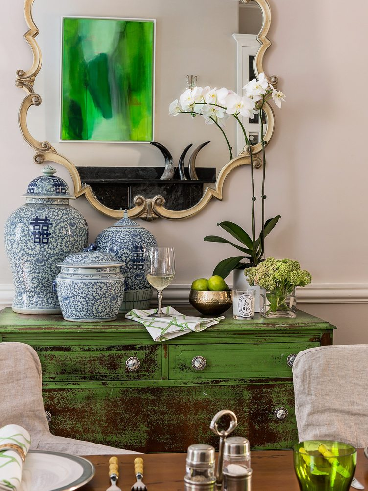 Shabby Chic Green Case Piece Decorated with Blue and White China Pots and Gold Mirror.