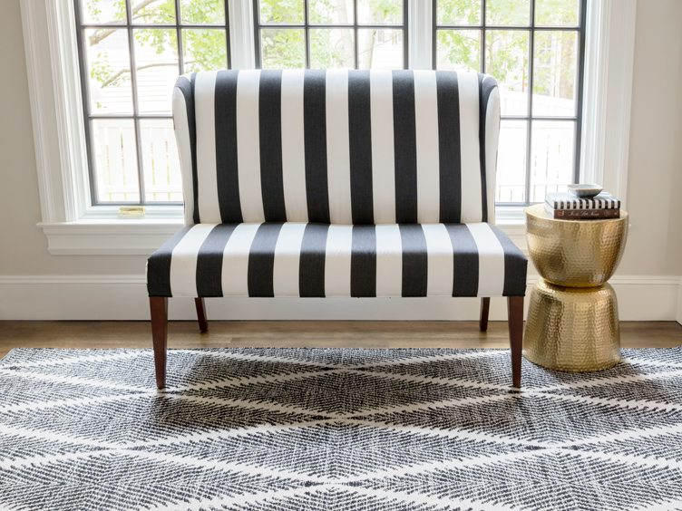 Black and white striped accent chair on geometric rug
