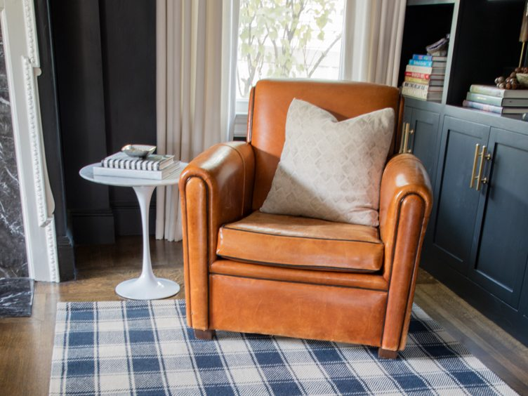 Brown leather armchair, and accent table on plaid rug
