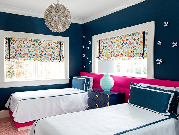 Kid's Room With Large Pink Headboard and Colorful Butterfly Print Window Shades.