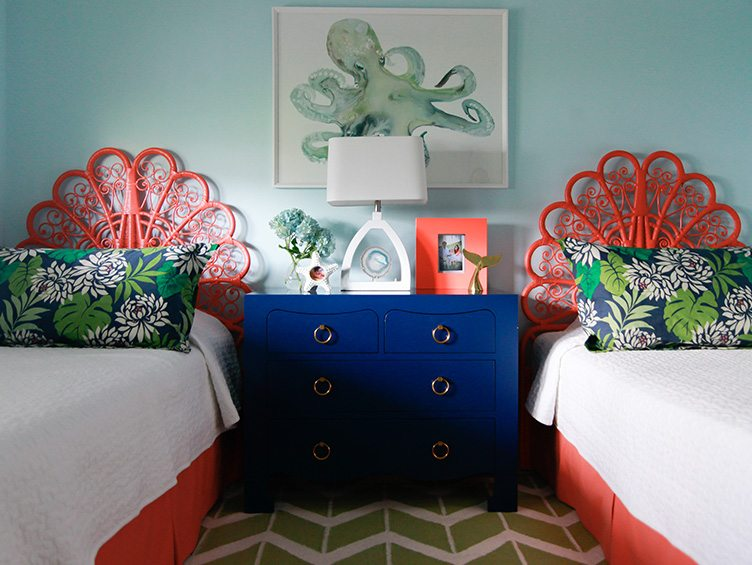 Twin Beds with matching Orange Headboards and Floral Decorative Pillows.