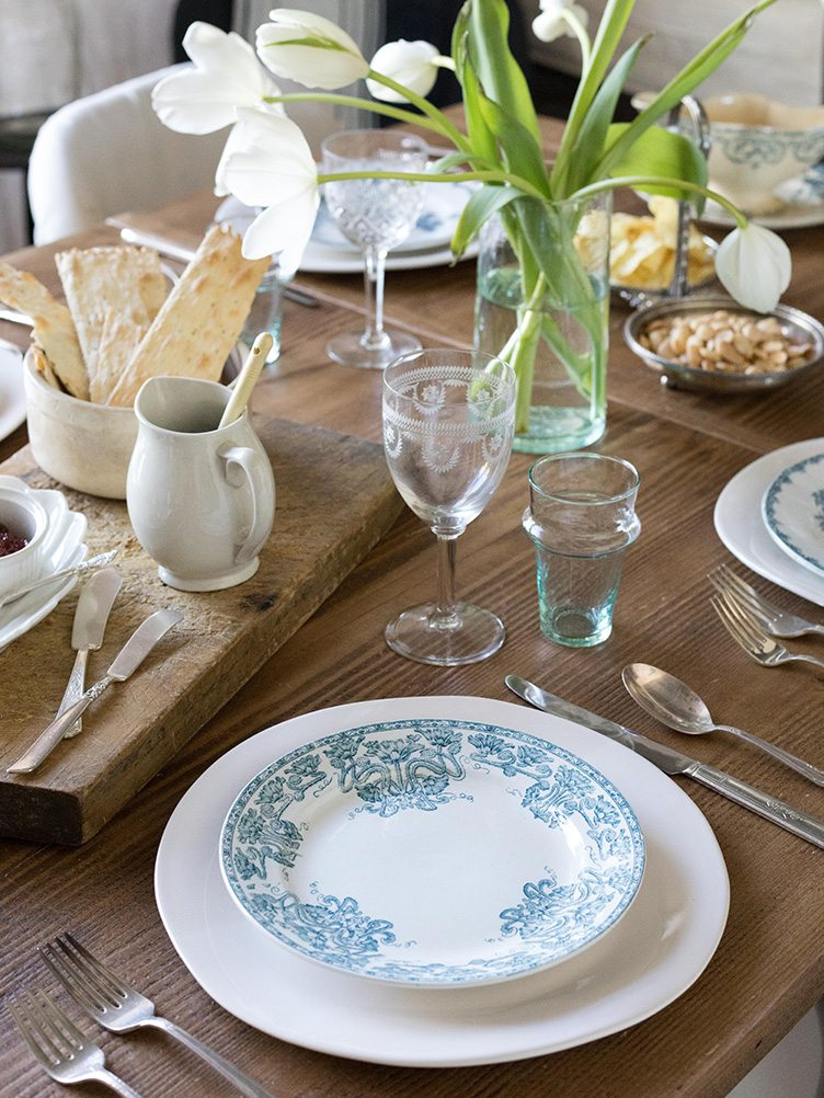 Chic Farmhouse Inspired Table Scape With Blue and White Patterned Plates and Wood Cheese Board.