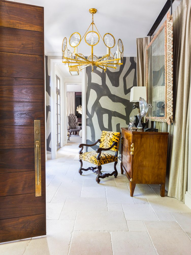 leather printed accent chair, vintage dresser, and gold chandelier in walkway