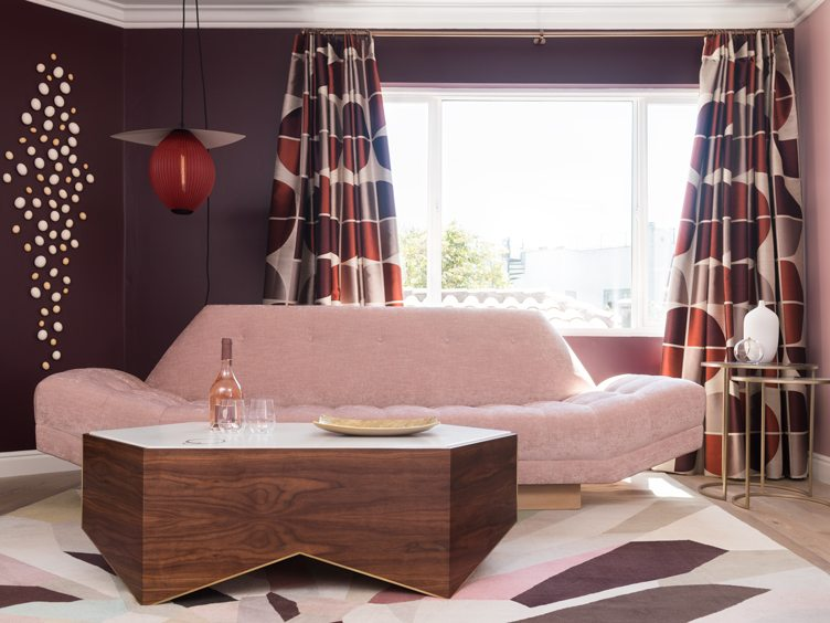 Contemporary Modern Living Room with Pink Sofa and Geometric Patterned Rug and Curtains.