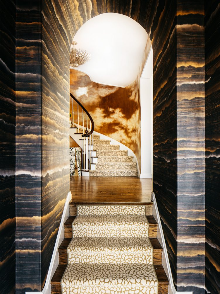 Glamorous Home Entryway with Wood Patterned Wallpaper and Spiral Staircase on Chairish.