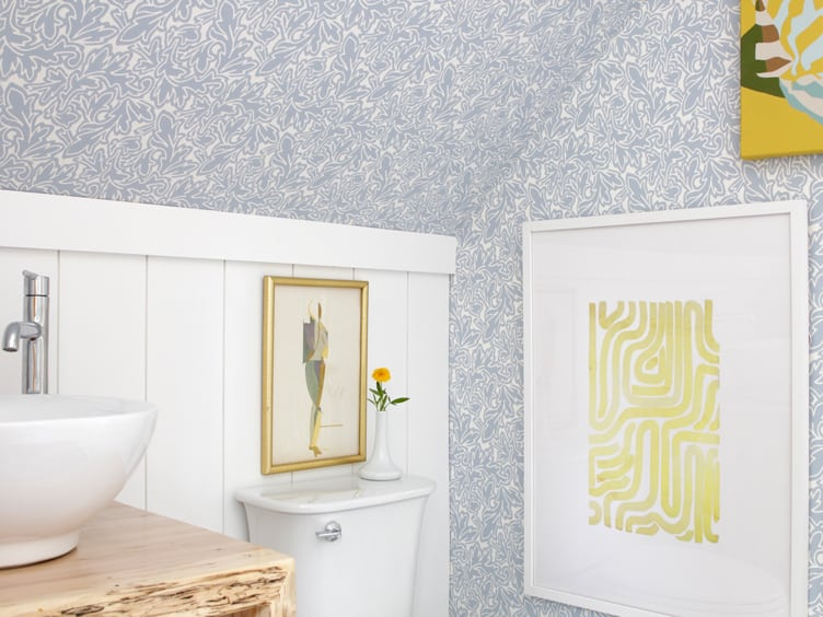 Light Blue and White Patterned Wallpaper in Bathroom with Yellow Print Art.