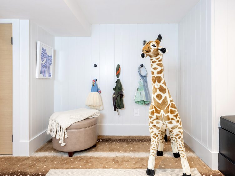 Children's Playroom with Large Stuffed Giraffe and Blue Bow Print Art on Chairish.