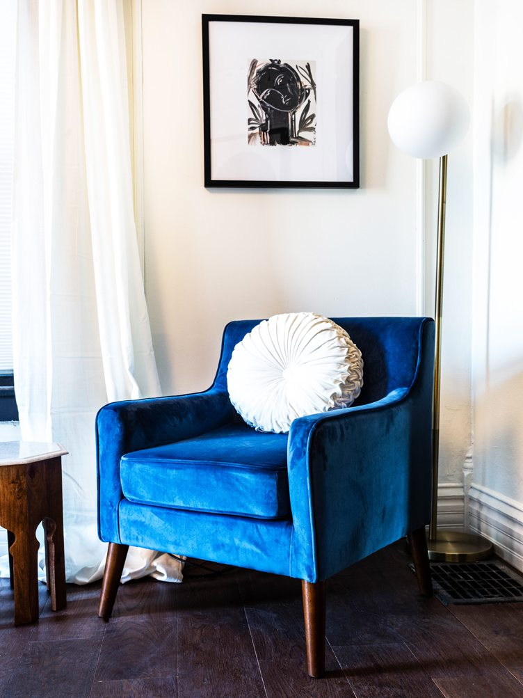 Modern Blue Velvet Armchair with White Pillow and Contemporary Print Artwork.