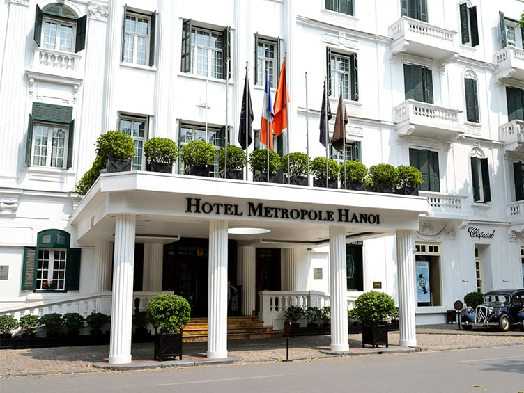 Hotel Metropole Hanoi Vietname white colonial green shutters historical pillars flags