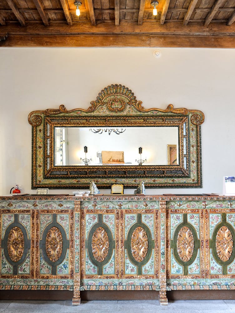 Historic Hotel Palacio Nazarenas Cusco Peru wide mirror ornate cabinets wood ceiling ancient antique