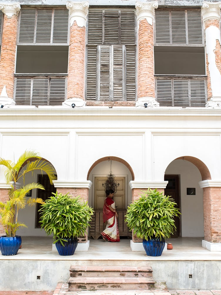 Rajbarai Bawali historic hotel calcutta india exterior large plants exposed brick white stairs wood shutters