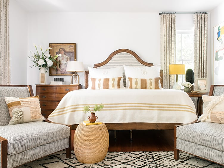 Bohemian Master Bedroom with Neutral Colors and Wooden Headboard and Vintage Hanging Art.
