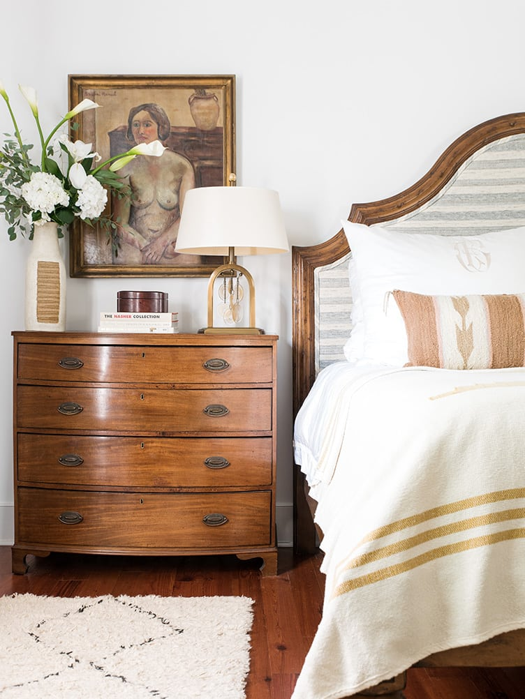 Classic Wooden Bedroom Dresser with Rustic Brass Table Lamp and Vintage Nude Hanging Art.