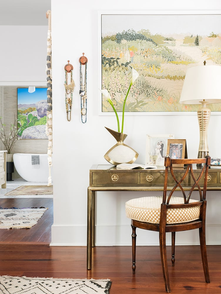 Classic Brass Desk with Large Vintage Hanging Art and Decorative Bohemian Hanging Necklaces.