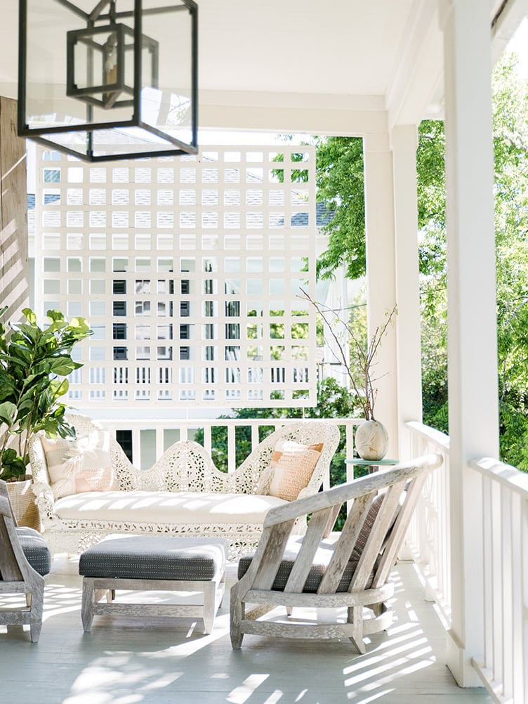 Shabby Chic Outdoor Porch with Brass Hanging Lantern and White Wicker Couch.
