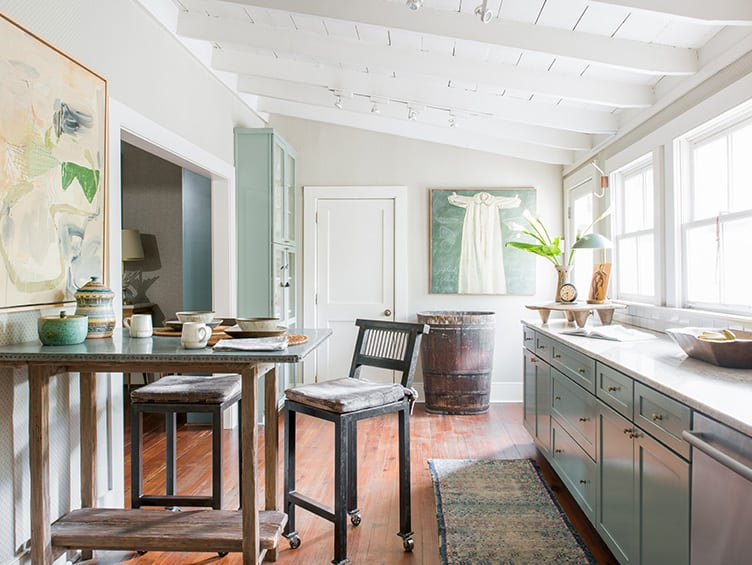 Rustic Kitchen With Blue Cabinets and Wooden Countertop Table Adorned With Clay Tableware.