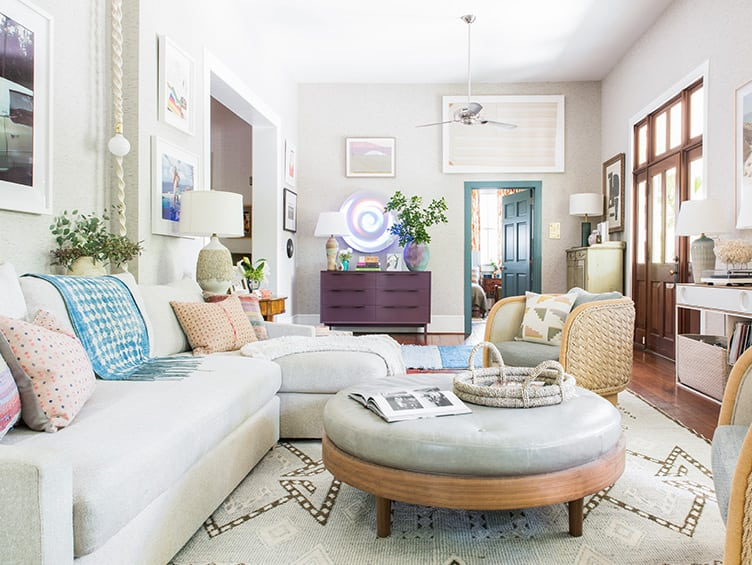 Eclectic Vintage Living Room With Round Cushioned Coffee Table and Hanging Art.