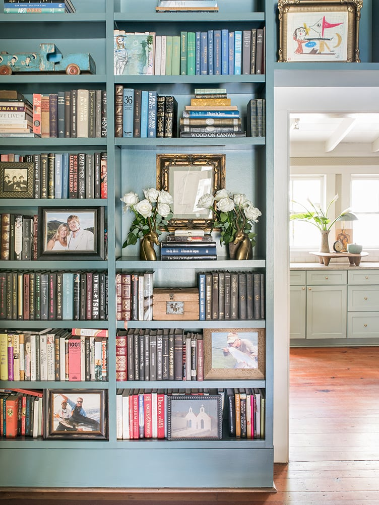 Blue Bookshelves Filled with Books Mixed in With Family Photographs and Vintage Art.