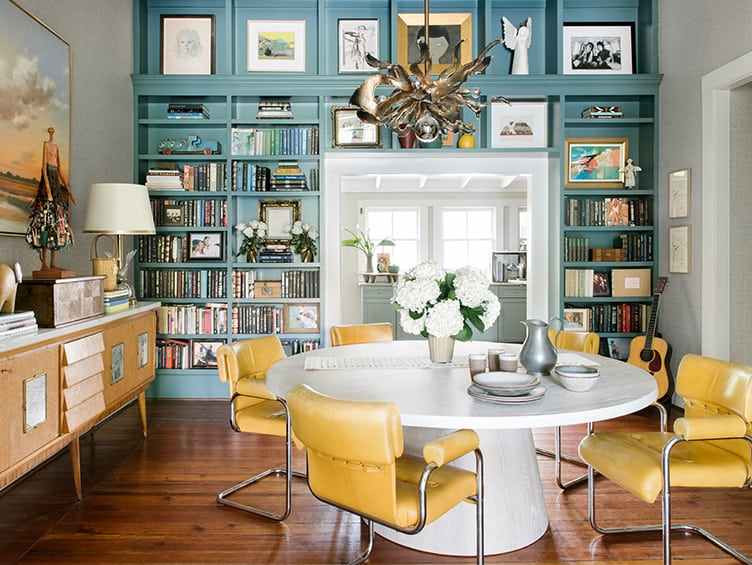 Home Library with Blue Bookshelves and Dining Table With Yellow Leather Chairs.
