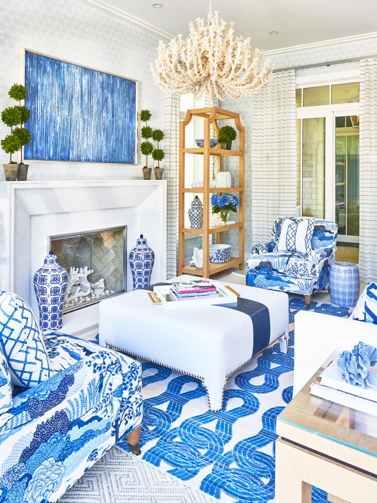 Patterned blue armchairs, and leather white ottoman, under eccentric cream chandelier