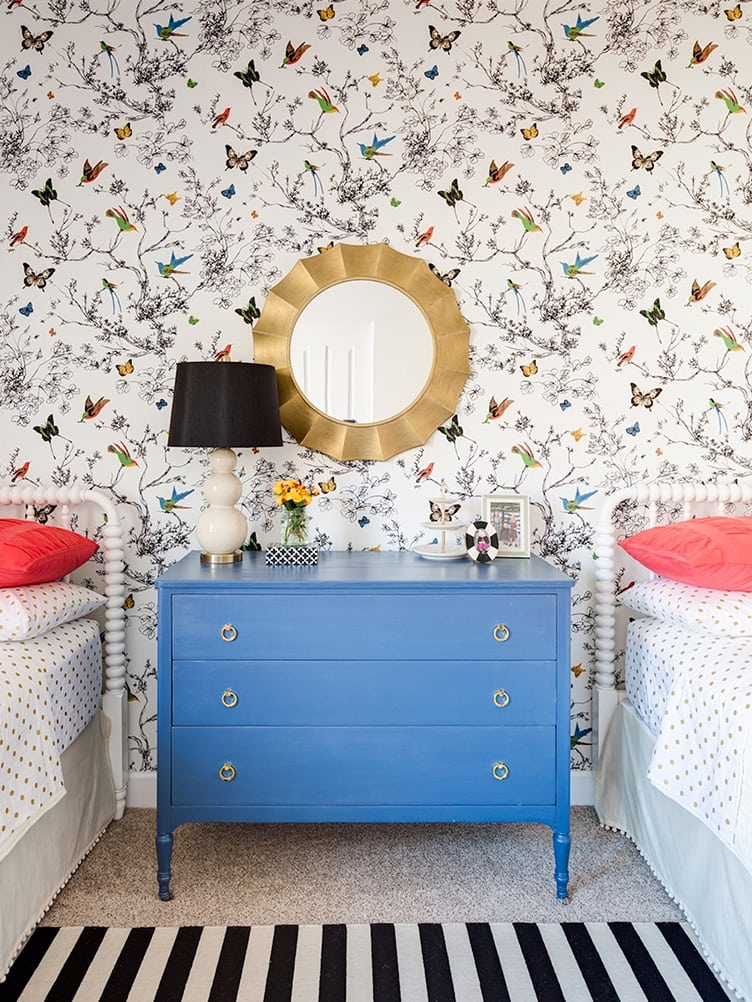 Bedroom with Colorful Butterfly Wallpaper and Blue Chest of Drawers.