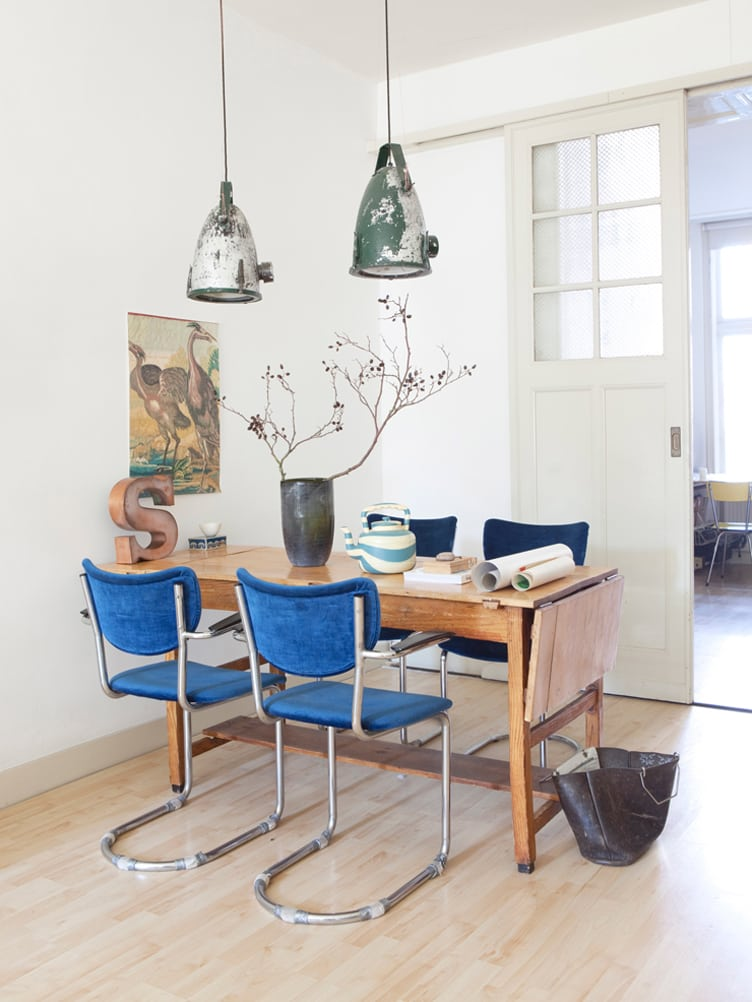Rustic Kitchen With Wooden Drop Leaf Table and Blue Velvet chairs and Large Hanging Lamps.