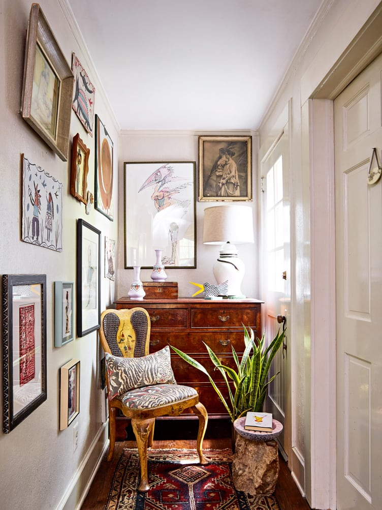 Collection of abstract, impressionist, and portraits with accent chair and wooden dresser in hallway