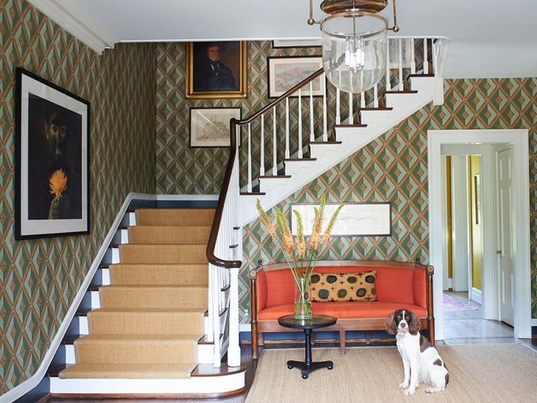 Traditional Home Entryway With Geometrically Patterned Wallpaper and Vintage Hanging Art.