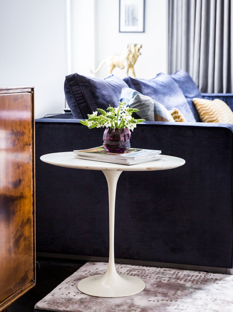 Mid Century Modern White Side Table With Flowers and Magazines Next to A Dark Blue Couch.