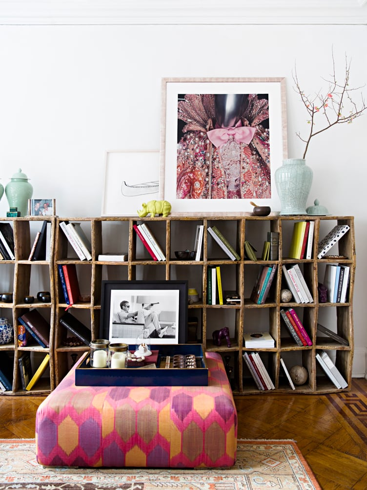 Shabby Chic Unfinished Wooden Bookshelf Next to Colorful Geometric Pattern Ottoman.