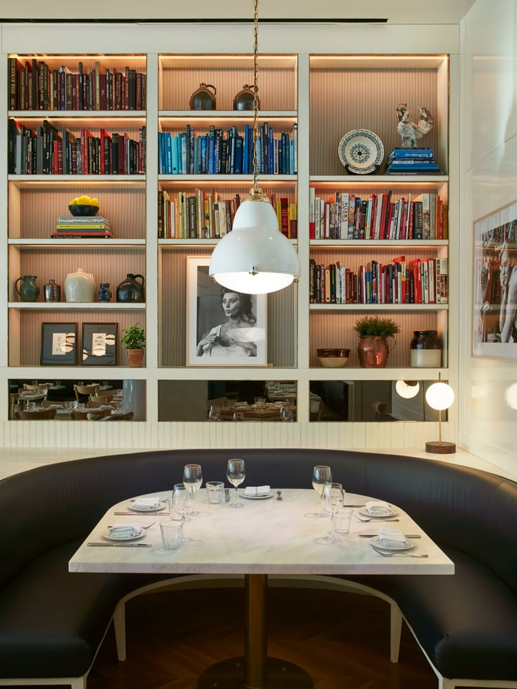 Chiara deRege interior design dining black leather marble table bookshelves color-coordinate