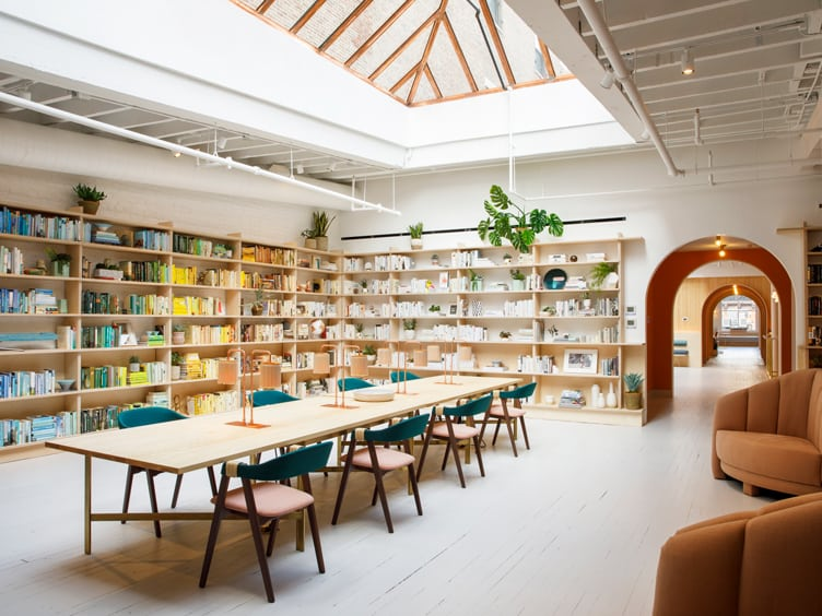 Chiara deRege coworking space color coordinated bookshelves wood industrial desk ceiling