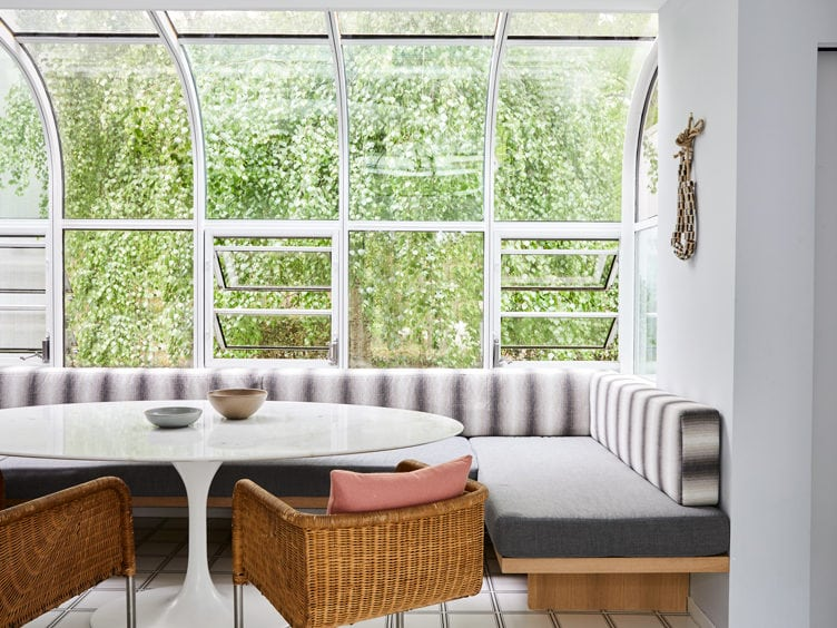 Contemporary Kitchen Table Area with Glass walls a Pair of Rattan Chairs.