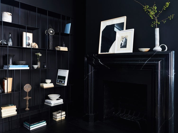 Living Room with Black Walls and Modern Black Metal Bookshelf and black Marble Fireplace.