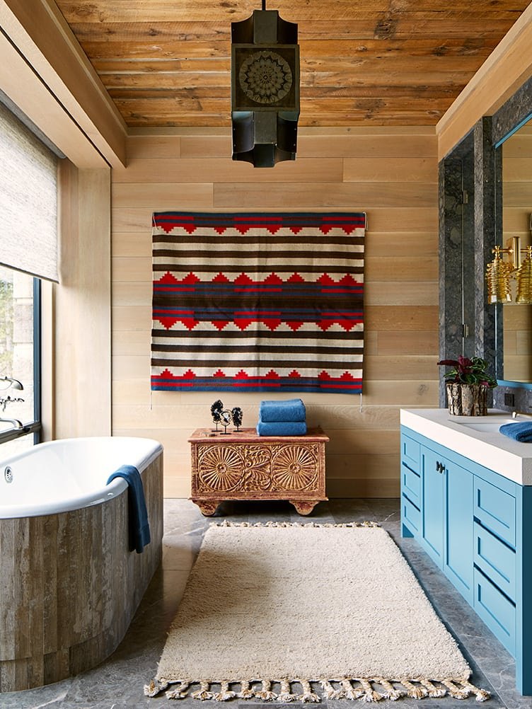 Hanging rug in rustic master bathroom with wood panel walls and blue accents.