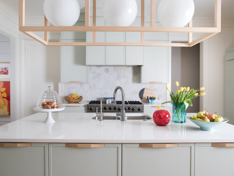 Kitchen with White Counters and Cabinets any White Circular Hanging Lamps.