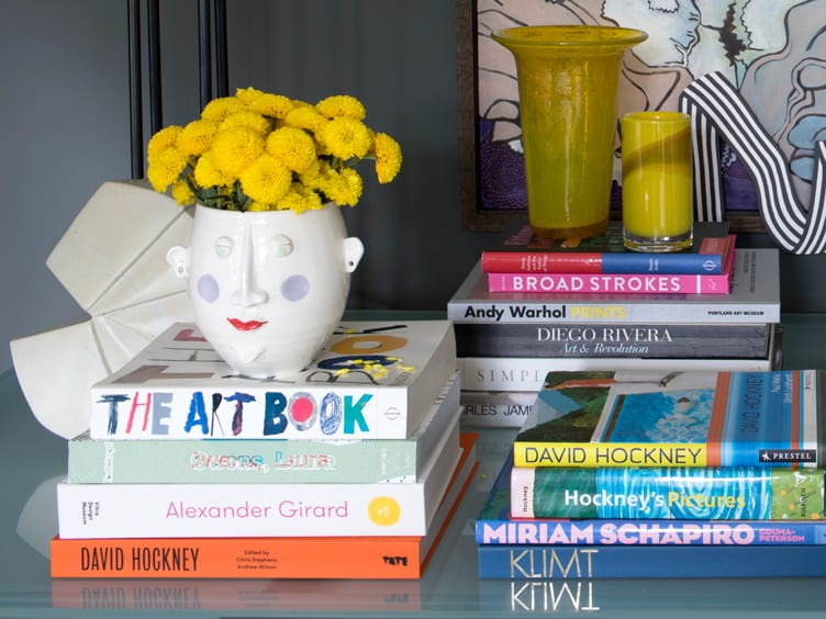 Coffee Table Decor of Books, Colorful Vases, and a Face Vase Containing Yellow Flowers